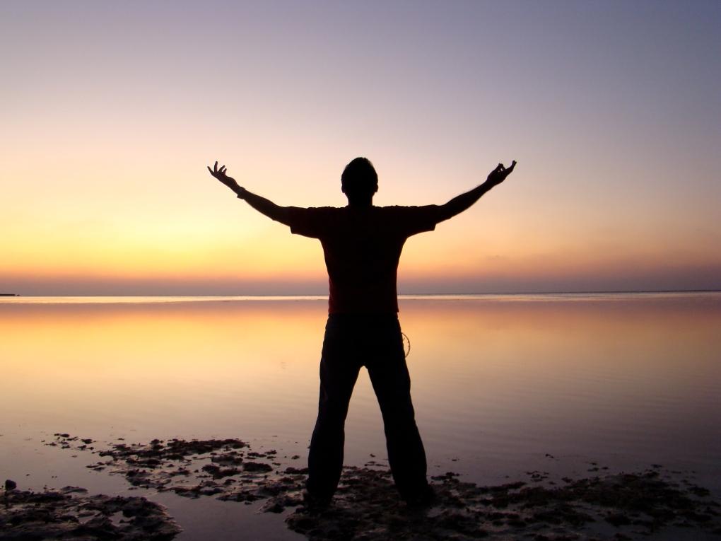 man worshipping at ocean